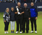 Ireland's Shane Lowry holding the Claret Jug trophy poses with his family on the 18th green after winning the British Open Golf Championships at Royal Portrush in Northern Ireland, Sunday, July 21, 2019.(AP Photo/Jon Super)