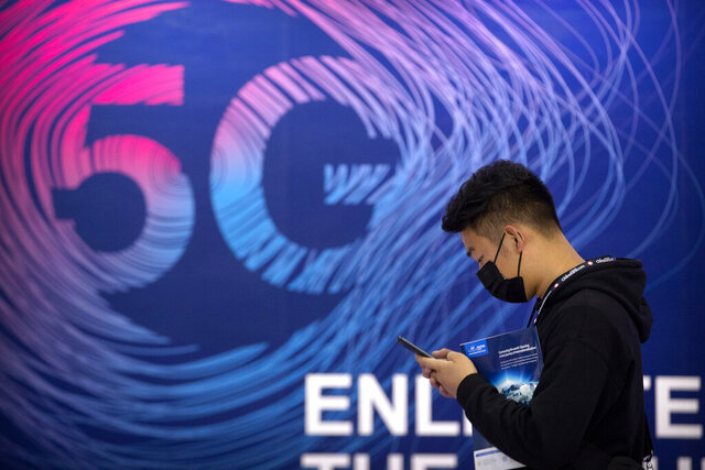 A man looks at his smartphone as he walks past a sign advertising 5G services at the PT Expo in Beijing, Wednesday, Sept. 14, 2020. China's leaders vowed Thursday, Oct. 29, 2020, to speed up its development as a self-reliant