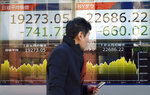 A man walks past at an electronic stock board showing Japan's Nikkei 225 index, left, and Dow Jones Industrial Average at a securities firm in Tokyo Friday, Jan. 4, 2019. (Japanese markets have tumbled as they reopened after the New Year holidays, while other Asian indexes are mixed after a technology-led sell-off on Wall Street. (AP Photo/Eugene Hoshiko)