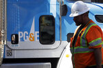 FILE - In this Aug. 15, 2019 file photo, a Pacific Gas & Electric worker walks in front of a truck in San Francisco. Pacific Gas & Electric has emerged from a contentious bankruptcy saga that began after its long-neglected electrical grid ignited wildfires in California that killed more than 100 people. PG&E announced Wednesday, July 1, 2020, it emerged from Chapter 11 bankruptcy and paid $5.4 billion in initial funds and 22.19 percent of its stock into a trust for victims of wildfires caused by its outdated equipment. (AP Photo/Jeff Chiu,File)