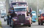 Migrants ride on the side of a truck moving along the highway, in hopes of reaching the distant United States, in San Pedro Sula, Honduras, early Wednesday, Jan. 15, 2020. Hundreds of Honduran migrants started walking and hitching rides Wednesday from the city of San Pedro Sula, in a bid to form the kind of migrant caravan that reached the U.S. border in 2018. (AP Photo/Delmer Martinez)