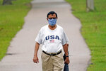 Shiraz Merchant wears a mask as he walks in a park Friday, June 26, 2020, in Houston. The number of COVID-19 cases continues to rise across the state. Texas Gov. Greg Abbott has said that the state is facing a