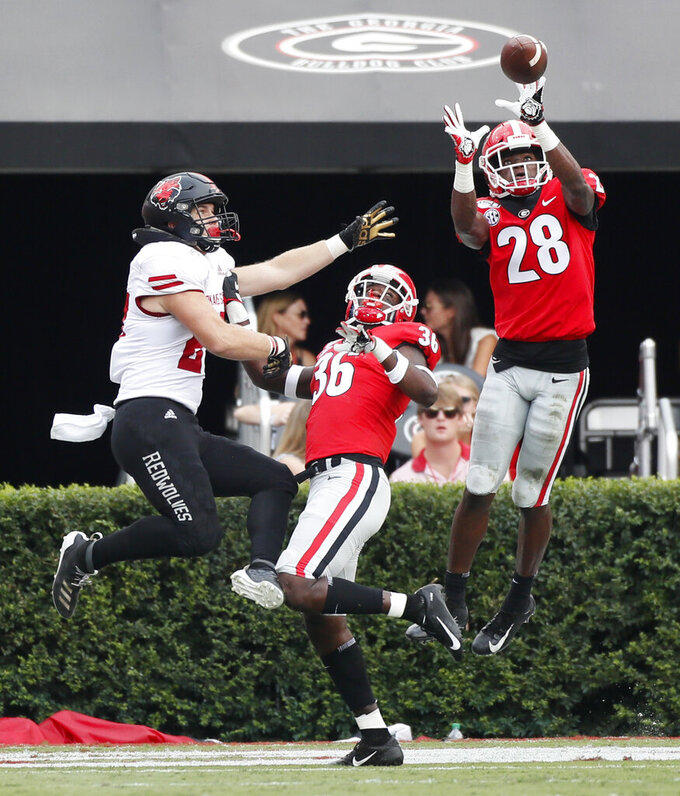 Georgia Louis Cine intercepts a pass in the end zone to persevere a shutout during the second half of an NCAA college football against Arkansas State NCAA football game in Athens, Ga. (Bob Andres/Atlanta Journal-Constitution via AP)