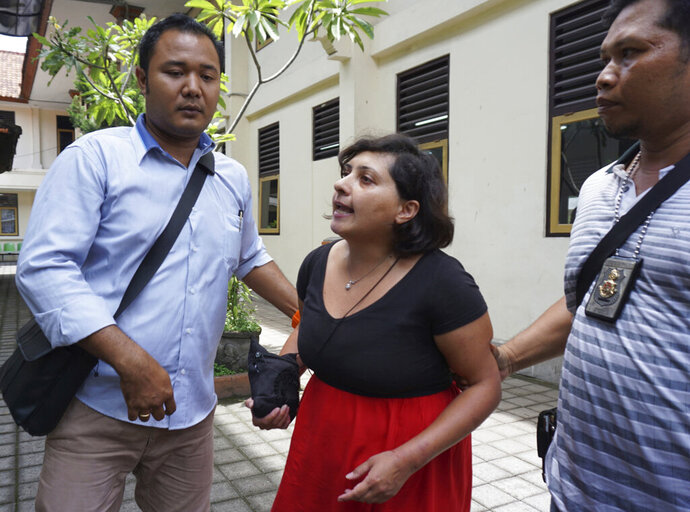 Auj-e Taqaddas of British, center, walks as she is escorted by investigators after her trial in Bali, Indonesia, Wednesday, Feb. 6, 2019. A British woman who slapped an immigration officer on the Indonesian tourist island of Bali after missing her flight due to an expired visa was sentenced Wednesday to six months in prison. (AP Photo)
