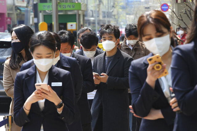 People wearing face masks to help protect against the spread of the new coronavirus wait to cast their early votes for the upcoming parliamentary election at a polling station in Seoul, South Korea, Friday, April 10, 2020. The elections will be held on April 15 at about 14,300 polling stations all over the nation to pick lawmakers. The new coronavirus causes mild or moderate symptoms for most people, but for some, especially older adults and people with existing health problems, it can cause more severe illness or death. (AP Photo/Ahn Young-joon)