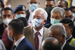 Former Malaysian Prime Minister Najib Razak, center, wearing a face mask with his supporters arrives at courthouse in Kuala Lumpur, Malaysia, Tuesday, July 28, 2020. Najib arrived for a verdict in the first of several corruption trials linked to the multibillion-dollar looting of the 1MDB state investment fund. (AP Photo/Vincent Thian)