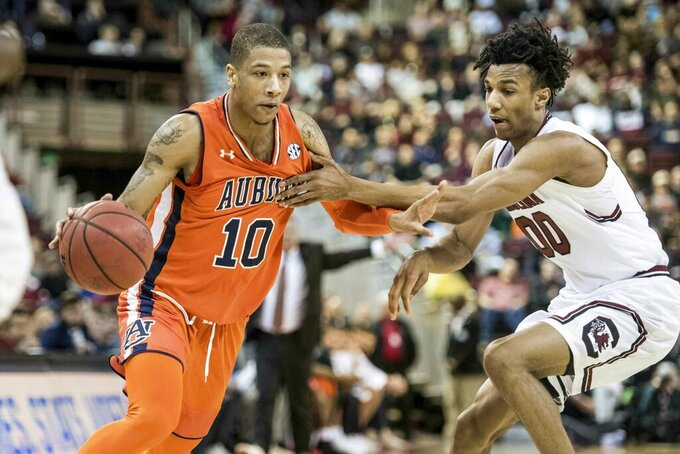 Auburn guard Samir Doughty (10) dribbles the ball against South Carolina guard A.J. Lawson (00) during the first half of an NCAA college basketball game Tuesday, Jan. 22, 2019, in Columbia, S.C. (AP Photo/Sean Rayford)