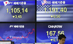A currency trader walks by the screens showing the foreign exchange rates at the foreign exchange dealing room in Seoul, South Korea, Monday, Sept. 16, 2019.  Asian stock markets were mixed Monday after crude prices surged following an attack on Saudi Arabia's biggest oil processing facility. (AP Photo/Lee Jin-man)