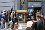 Jamie Foxx, right of podium, and Mayor London Breed, left of podium, take part in a