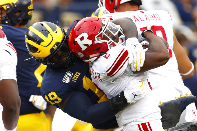 Michigan defensive lineman Kwity Paye (19) stops Rutgers running back Raheem Blackshear (2) in the first half of an NCAA college football game in Ann Arbor, Mich., Saturday, Sept. 28, 2019. (AP Photo/Paul Sancya)