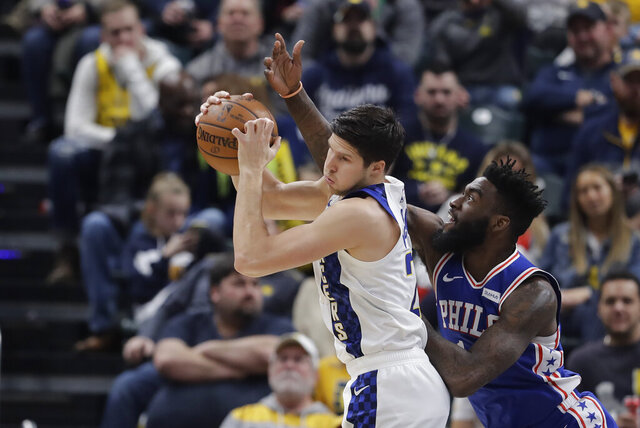 Indiana Pacers' Doug McDermott (20) grabs a rebound against Philadelphia 76ers' Norvel Pelle (14) during the first half of an NBA basketball game, Tuesday, Dec. 31, 2019, in Indianapolis. (AP Photo/Darron Cummings)