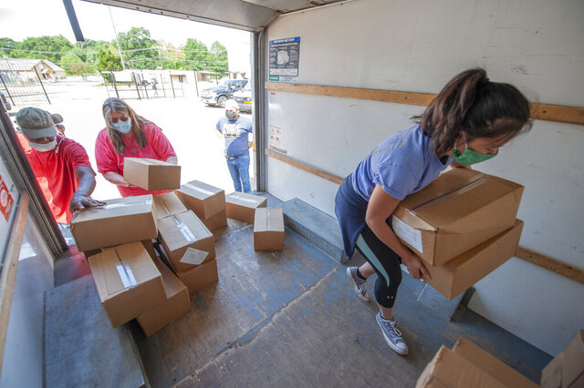 In this Tuesday, May 19, 2020 photo, a Stewpot Community Services volunteer, right,  loads boxes of fresh produce into a truck for the nonprofit Grace House in Jackson, Miss. Throughout the morning, 500 boxes of fresh produce, part of the Farmers to Families Food Box program, were distributed to 12 local groups from the Stewpot location in Jackson, Miss. The Farmers to Families Food Box program is part of the USDA Coronavirus Farm Assistance Program. (Barbara Gauntt/The Clarion-Ledger via AP)