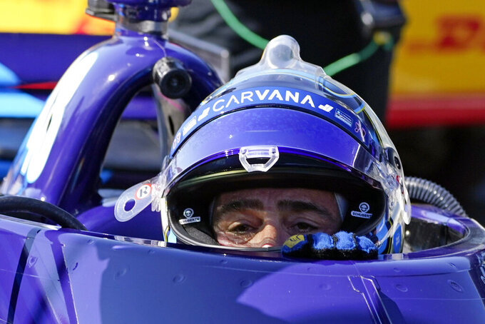 FILE - In this May 14, 2021, file photo, Jimmie Johnson climbs out of his car following practice for the IndyCar auto race at Indianapolis Motor Speedway in Indianapolis.  When a pair of poor finishes cost Alex Palou the IndyCar points lead, the second-year driver found teammate Johnson for a pair of pep talks. Johnson may be an IndyCar rookie on the track, but the intangibles he brings to Chip Ganassi Racing as a seven-time NASCAR champion are invaluable. (AP Photo/Darron Cummings, File)
