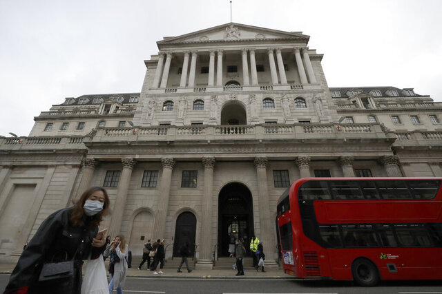FILE - In this file photo dated Wednesday, March 11, 2020, pedestrians wearing face masks walk past the Bank of England in London.  The Bank of England kept its main interest rate unchanged at the record low of 0.1% on Thursday Sept. 17, 2020, as it waits to see how the economy recovers from recession and what Britain's future trade relationship with the European Union will be. (AP Photo/Matt Dunham, FILE)