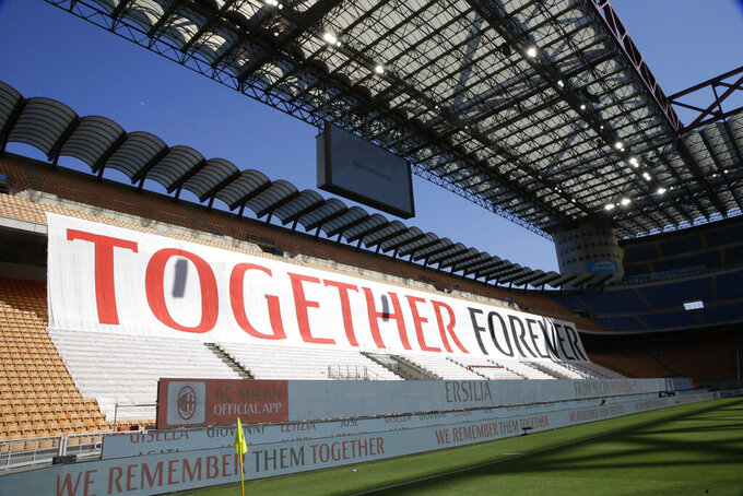 """A giant banner is displayed during the Serie A soccer match between AC Milan and Roma, at the San Siro Stadium in Milan, Sunday, June 28, 2020. It was Milan's first home match since the lockdown and the team put up a huge banner along one side of the empty San Siro stadium that read """"Together Forever,"""" dedicated to coronavirus victims. The Lombardy region of which Milan is the capital was the hardest hit area in Italy with more than 16,000 deaths. (AP Photo/Luca Bruno)"""