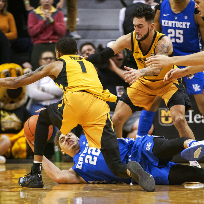 Kentucky's Reid Travis, bottom, looks to pass the ball from the floor as Missouri's Xavier Pinson, left, and Jordan Geist, right, move in during the first half of an NCAA college basketball game Tuesday, Feb. 19, 2019, in Columbia, Mo. Kentucky won 66-58. (AP Photo/L.G. Patterson)