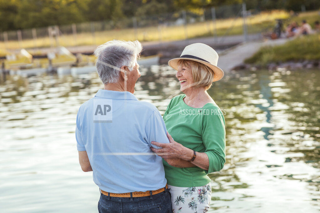 Cheerful senior couple looking at each other while standing by lake