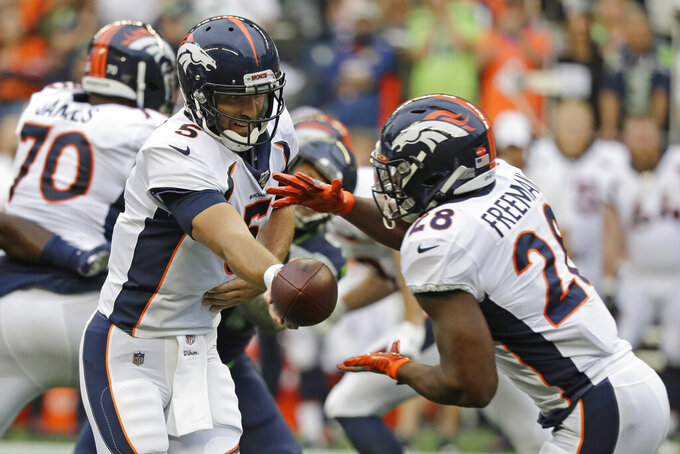 Denver Broncos quarterback Joe Flacco (5) hands off to running back Royce Freeman, right, during the first half of the team's NFL football preseason game against the Seattle Seahawks, Thursday, Aug. 8, 2019, in Seattle. (AP Photo/Elaine Thompson)