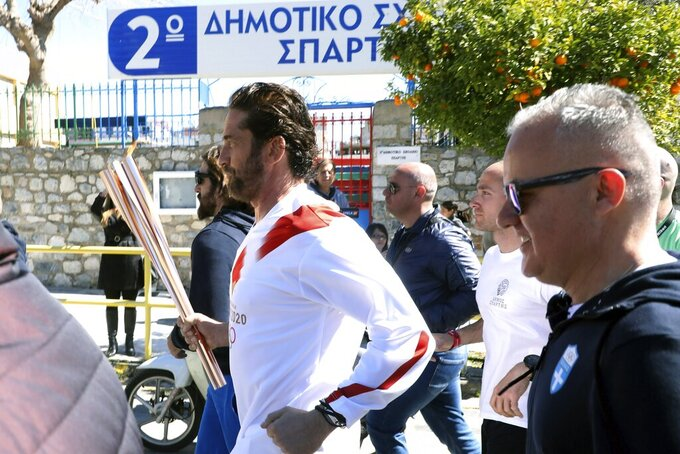 "US actor Gerard Butler runs as a torchbearer during the Olympic torch relay of the 2020 Tokyo Olympic Games in the southern Greek town of Sparta, Friday, March 13, 2020. Greece's Olympic committee says it is suspending the rest of its torch relay for the Olympic flame due to the ""unexpectedly large crowd"" that gathered to watch despite repeated requests for the public to stay away to prevent the spread of the new coronavirus. (AP Photo)"