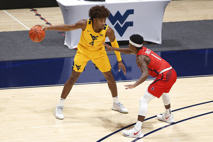 West Virginia guard Miles McBride (4) is defended by Richmond guard Blake Francis (1) during the second half of an NCAA college basketball game Sunday, Dec. 13, 2020, in Morgantown, W.Va. (AP Photo/Kathleen Batten)