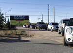 Voters line up in their cars ahead of the opening of a polling station on Saturday, Oct. 17, 2020, in Santa Fe, N.M. Early voting began Saturday and hundreds came to vote in person or drop off absentee ballots as part of the 2020 presidential election. (AP Photo/Cedar Attanasio)