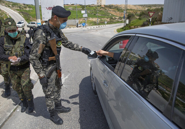 Palestinian security forces are deployed to enforce new government measures against the coronavirus, in the West Bank city of Ramallah, Monday, March 23, 2020. On Sunday, Palestinian Prime Minister Mohammad Shtayyeh declared a two week set of strict precautionary measures that include confining residents to their homes, restricting movement between cities and deploying security forces, along with other measures to contain the COVID-19 outbreak. (AP Photo/Nasser Nasser)