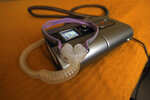 The sleep apnea breathing device that Joelle Dobrow uses at her home in Los Angeles lies on her bed on Thursday, July 12, 2018. It's been two decades since doctors fully recognized that breathing that stops and starts during sleep is tied to a host of health issues, even early death, but there still isn't a treatment that most people find easy to use. Dobrow said it took her seven years to find one she liked.