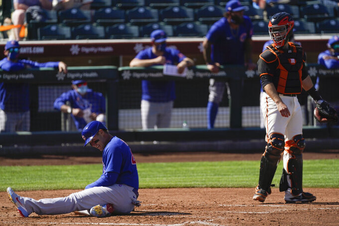 Chicago Cubs' Anthony Rizzo, left, reacts after being tagged out by San Francisco Giants catcher Buster Posey, right, at home plate during the fourth inning of a spring training baseball game Wednesday, March 10, 2021, in Scottsdale, Ariz. (AP Photo/Ashley Landis)