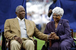 FILE - In this April 8, 2014, file photo, Hank Aaron, left, sits with his wife Billye, during a ceremony celebrating the 40th anniversary of his 715th home run before the start of a baseball game between the Atlanta Braves and the New York Mets in Atlanta. Hank Aaron, who endured racist threats with stoic dignity during his pursuit of Babe Ruth but went on to break the career home run record in the pre-steroids era, died early Friday, Jan. 22, 2021. He was 86. The Atlanta Braves said Aaron died peacefully in his sleep. No cause of death was given. (AP Photo/David Goldman, File)