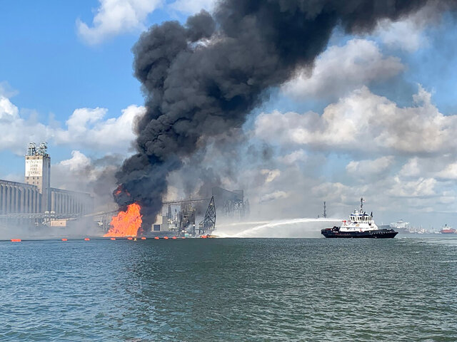 CORRECTS TO PROPANE PIPELINE INSTEAD OF A NATURAL GAS PIPELINE - In this photo released by the U.S. Coast Guard, Coast Guard crews respond to a dredge on fire in the Port of Corpus Christi Ship Channel, Aug. 21, 2020 in Corpus Christi, Texas. Authorities say several people have been hospitalized after an explosion at the Texas port when a dredging vessel hit a propane gas pipeline in the water. (U.S. Coast Guard via AP)