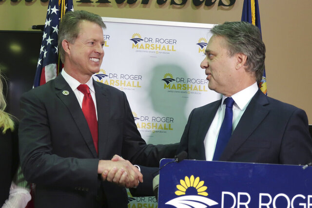 U.S. Rep. Roger Marshall, left, R-Kan., shakes hands with former Kansas Gov. Jeff Colyer, right, after receiving Colyer's endorsement in the U.S. Senate race, Monday, Feb. 24, 2020, in Topeka, Kan. Colyer is urging Republicans to unite behind Marshall as he battles former Kansas Secretary of State Kris Kobach for the GOP nomination. (AP Photo/John Hanna)
