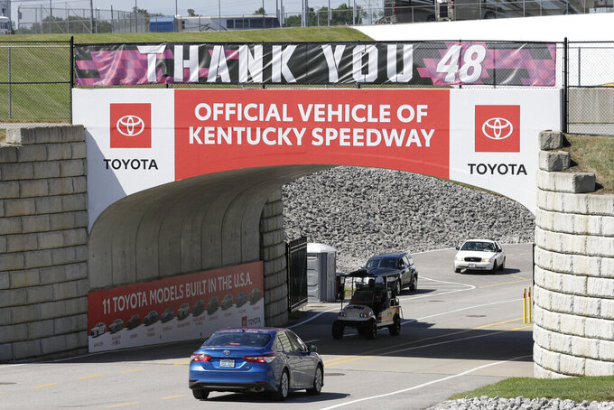An entrance sign for Kentucky Speedway is decorated with a banner honoring driver Jimmie Johnson before a NASCAR Cup Series auto race Sunday, July 12, 2020, in Sparta, Ky. NASCAR's nicest guy will run his final race this week and close a remarkable career. Jimmie Johnson's record-tying seven Cup titles are well celebrated, but his charitable work goes less noticed. The Jimmie Johnson Foundation has donated more than $12 million to schools and programs since it launched. (AP Photo/Mark Humphrey)