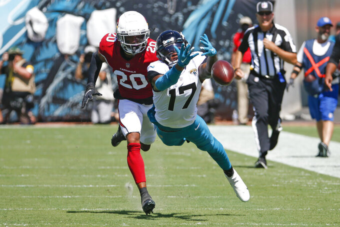 Jacksonville Jaguars wide receiver D.J. Chark (17) dives but can't make a catch as he is defended by Arizona Cardinals cornerback Marco Wilson (20) during the first half of an NFL football game, Sunday, Sept. 26, 2021, in Jacksonville, Fla. (AP Photo/Stephen B. Morton)