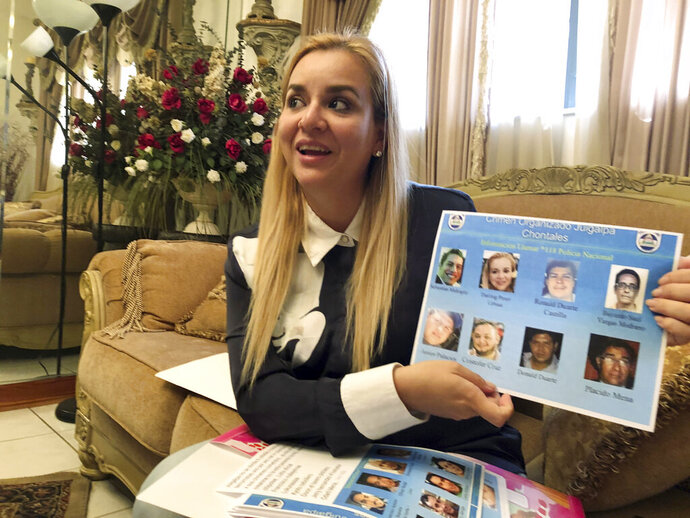 In this Oct. 15, 2018 photo, Darling Perez shows a copy of a Nicaraguan government wanted poster in which she is listed, during an interview in Miami. Perez, a pediatrician, worked at a public hospital in Nicaragua and was told not to take care of patients who were hurt during protests. She refused and began helping wounded students at private clinics. Perez, her husband and 12-month-old baby, all of whom arrived in the U.S. on tourist visas, are now seeking asylum in the U.S. (AP Photo/Gisela Salomon)