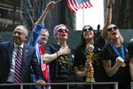 FILE - In this July 10, 2019, file photo, from left to right, U.S. Soccer Federation President Carlos Cordeiro, New York Mayor Bill de Blasio and U.S. women's soccer players Megan Rapinoe and Alex Morgan joins teammates and others as the U.S. women's soccer team is celebrated with a ticker tape parade along the Canyon of Heroes in New York. Rapinoe is enjoying the whirlwind of a two-time World Cup winner. She picked up the FIFA Player of the Year award in Milan rocking a deeper shade of lavender hair, sent off retiring U.S. coach Jill Ellis with an undefeated victory tour and kept up the fight for pay equity against the U.S. Soccer Federation. (AP Photo/Craig Ruttle, File)