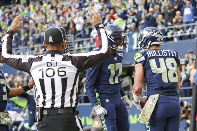 Seattle Seahawks tight end Jacob Hollister, right, celebrates with wide receiver Malik Turner (17) as down judge Patrick Holt  (106) signals Hollister's touchdown against the Tampa Bay Buccaneers during the first half of an NFL football game, Sunday, Nov. 3, 2019, in Seattle. (AP Photo/Scott Eklund)