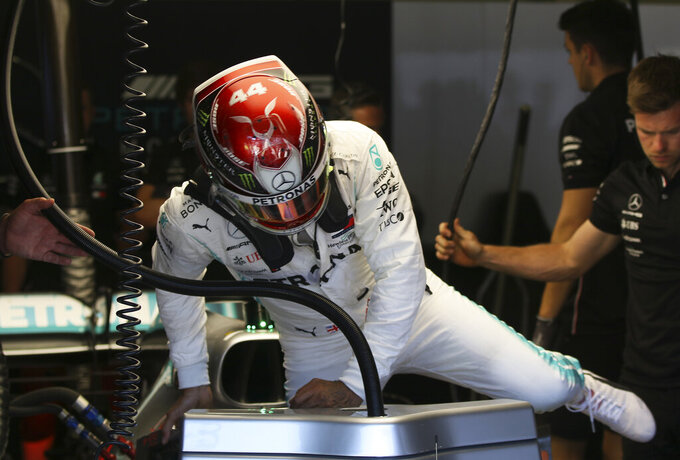 Mercedes driver Lewis Hamilton of Britain gets into his car cockpit during the first free practice session for the Austrian Formula One Grand Prix at the Red Bull Ring racetrack in Spielberg, southern Austria, Friday, June 28, 2019. The race will be held on Sunday. (AP Photo/Ronald Zak)