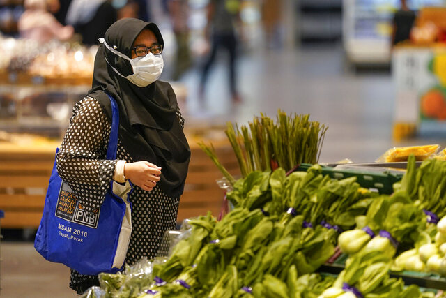 A shopper wearing a face mask to help curb the spread of the coronavirus looks at produce and a grocery in Putrajaya, Malaysia, Monday, Oct. 5, 2020. Prime Minister Muhyiddin Yassin says he will self-quarantine after a Cabinet minister he was in contact with tested positive for the coronavirus. (AP Photo/Vincent Thian)