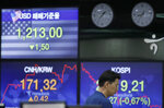 A currency trader walks by the screens showing the Korea Composite Stock Price Index (KOSPI), right, and the foreign exchange rates at the foreign exchange dealing room in Seoul, South Korea, Friday, June 19, 2020. Asian stock markets were mixed Friday after Wall Street closed little-changed amid as optimism about a possible global economic recovery was tempered by concern over rising coronavirus infections. (AP Photo/Lee Jin-man)