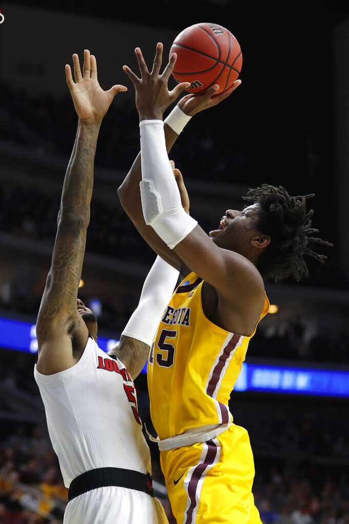 Minnesota center Daniel Oturu shoots over Louisville center Malik Williams, left, during a first round men's college basketball game in the NCAA Tournament, Thursday, March 21, 2019, in Des Moines, Iowa. (AP Photo/Charlie Neibergall)