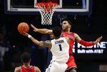 Xavier guard Paul Scruggs (1) attempts to shoot against St. John's guard Julian Champagnie, right, during the second half of an NCAA college basketball game, Sunday, Jan. 5, 2020, in Cincinnati. (AP Photo/Gary Landers)