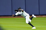 Miami Marlins center fielder Lewis Brinson (25) makes a running catch for the third out on a ball hit by Atlanta Braves' Travis d'Arnaud in the eighth inning in Game 3 of a baseball National League Division Series, Thursday, Oct. 8, 2020, in Houston. (AP Photo/David J. Phillip)