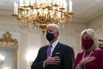 President Joe Biden, accompanied by first lady Jill Biden, places his hand over his heart during a performance of the national anthem, during a virtual Presidential Inaugural Prayer Service in the State Dinning Room of the White House, Thursday, Jan. 21, 2021, in Washington. (AP Photo/Alex Brandon)
