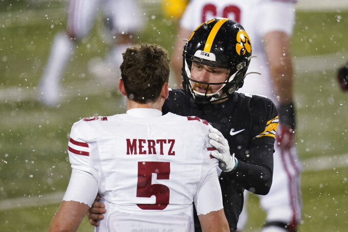Iowa quarterback Spencer Petras, right, talks with Wisconsin quarterback Graham Mertz (5) after an NCAA college football game, Saturday, Dec. 12, 2020, in Iowa City, Iowa. Iowa won 28-7. (AP Photo/Charlie Neibergall)