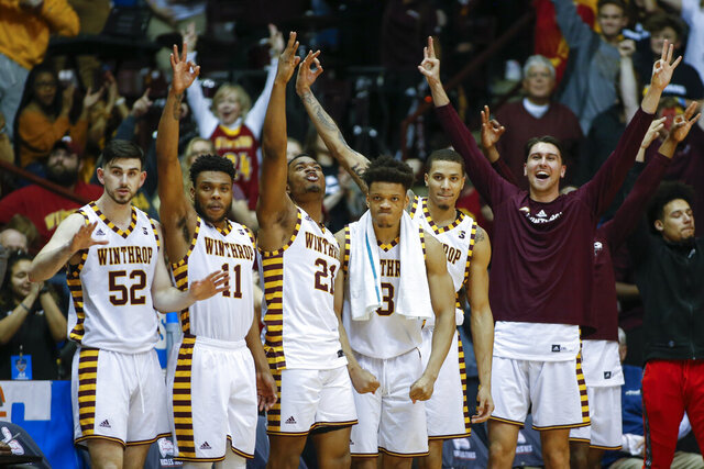 FILE - In this March 8, 2020 file photo, Winthrop players celebrate in the closing seconds of an NCAA college basketball game against Hampton for the Big South tournament championship in Rock Hill, S.C. Winthrop has Division I's best record in men's basketball yet the Eagles continue to soar off anyone's national radar. The unranked Eagles have won all 15 games this season and have the longest win streak at 20.(AP Photo/Nell Redmond, File)