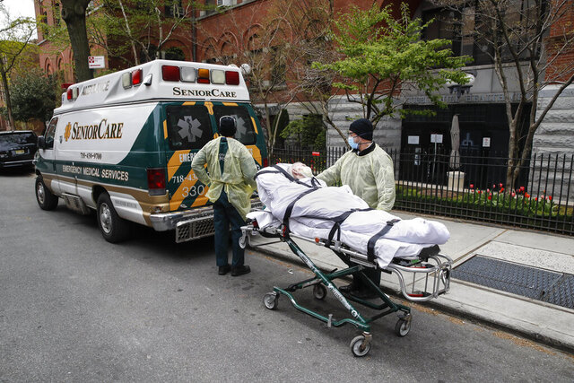 FILE - In this April 17, 2020, file photo, a patient is wheeled out of Cobble Hill Health Center by emergency medical workers in the Brooklyn borough of New York. New York Gov. Andrew Cuomo is facing blistering criticism over an internal report that found no strong link between a controversial state directive that sent thousands of recovering coronavirus patients into nursing homes and some of the nation's deadliest nursing home outbreaks. Scientists, health care professionals and elected officials assailed the report released last week for failing to address the actual impact of the March 25 order, which by the state's own count ushered more than 6,300 recovering virus patients into nursing homes at the height of the pandemic. (AP Photo/John Minchillo, File)