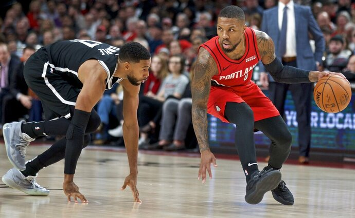 Portland Trail Blazers guard Damian Lillard, right, dribbles around Brooklyn Nets guard Garrett Temple during the first half of an NBA basketball game in Portland, Ore., Friday, Nov. 8, 2019. (AP Photo/Craig Mitchelldyer)