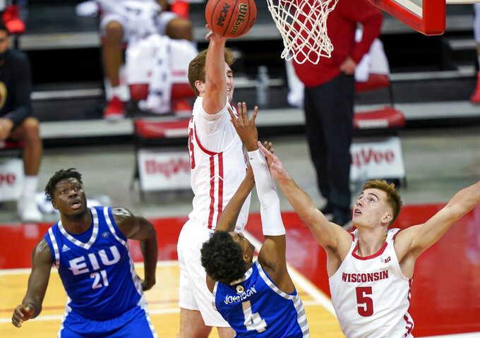 Wisconsin's Nate Reuvers, top left, and Carter Higginbottom defend on a shot by Eastern Illinois' Marvin Johnson (4) during the first half of an NCAA college basketball game Wednesday, Nov. 25, 2020, in Madison, Wis. (AP Photo/Andy Manis)