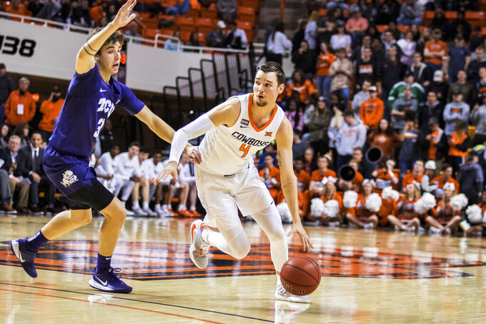 Oklahoma State's Thomas Dziagwa dribbles around TCU guard Francisco Farabello during an NCAA college basketball game Wednesday, Feb. 5, 2020, in Stillwater, Okla. (Devin Lawrence/Tulsa World via AP)
