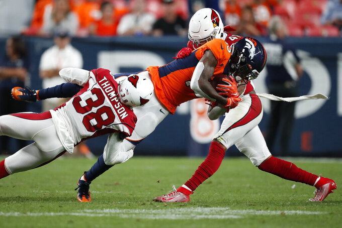 Denver Broncos wide receiver Juwann Winfree is hit by Arizona Cardinals defensive back Jalen Thompson (38) and defensive back Nate Brooks (41) during the second half of an NFL preseason football game, Thursday, Aug. 29, 2019, in Denver. (AP Photo/David Zalubowski)